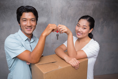 Happy couple holding house key and leaning on moving box in their new home photo