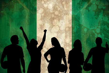 Silhouettes of football supporters against nigeria flag in grunge effect photo