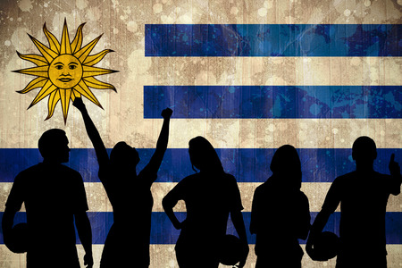 Silhouettes of football supporters against uruguay flag in grunge effect photo