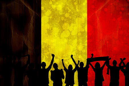 Silhouettes of football supporters against belgium flag in grunge effect photo