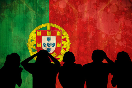 Silhouettes of football supporters against portugal flag in grunge effect photo