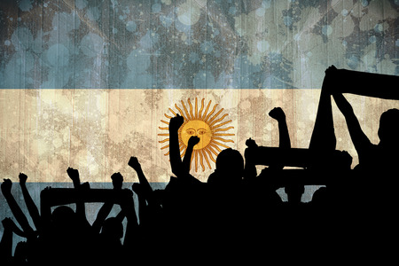 Silhouettes of football supporters against argentina flag in grunge effect photo