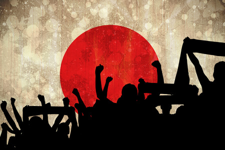Silhouettes of football supporters against japan flag in grunge effect photo