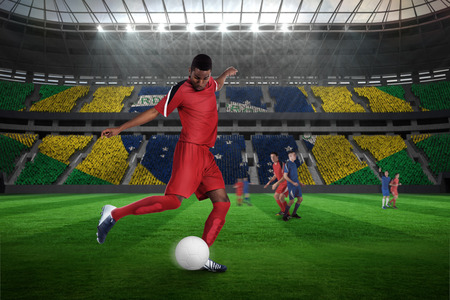 Football player in red kicking against large football stadium with brasilian fans photo