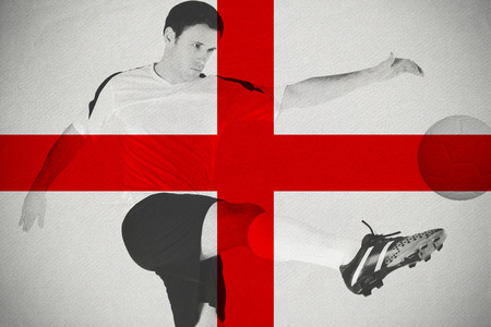 Football player in white kicking against england national flag photo