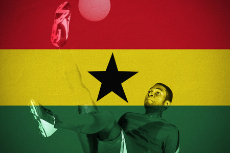 Football player in red kicking against ghana national flag photo
