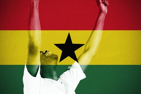 Excited handsome football fan cheering against ghana national flag photo