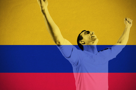 Excited football fan cheering against colombia national flag photo