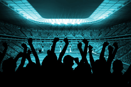 Silhouettes of football supporters against large football stadium with lights photo