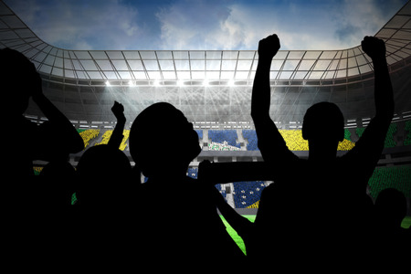 Silhouettes of football supporters against large football stadium with brasilian fans photo