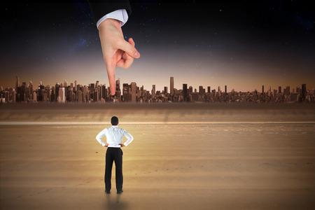 mujer mirando el horizonte: Apuntando gigante mano en el empresario de pie de nuevo a la c�mara con las manos en las caderas contra el paisaje urbano en el horizonte Foto de archivo