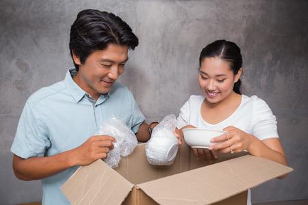 Coppia felice disimballaggio caselle in movimento nella loro nuova casa photo