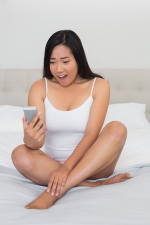 Shocked woman sitting on bed reading a text at home in bedroom photo