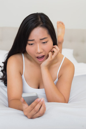 Shocked woman lying on bed holding smartphone at home in bedroom photo