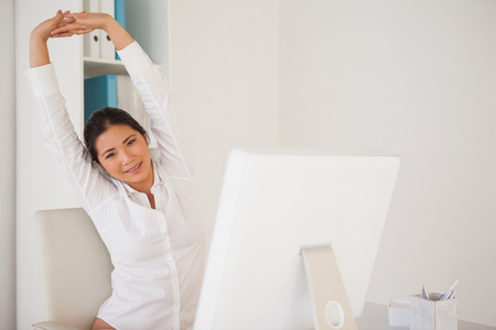 Casual businesswoman stretching at her desk in her office photo