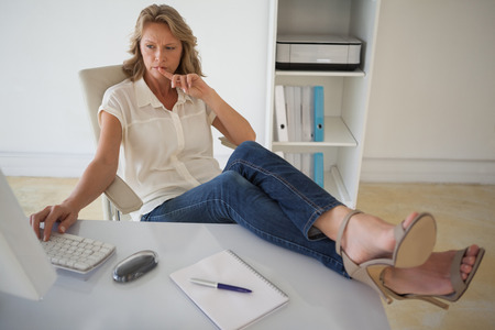 Casual businesswoman working with her feet up at desk in her office photo