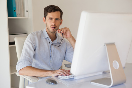 Casual businessman thinking at his desk in his office photo