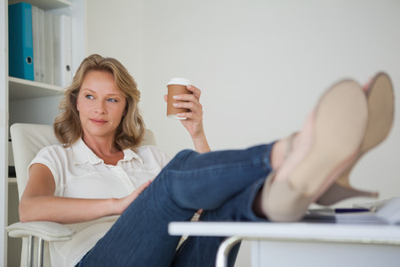 Casual businesswoman having a coffee with her feet up at desk in her office photo