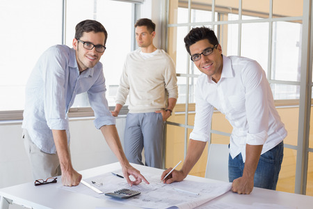 Casual architecture team working together at desk smiling at camera in the office photo