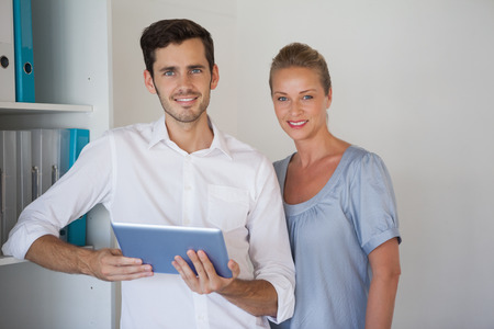 Casual business team smiling at camera man holding tablet in the office photo