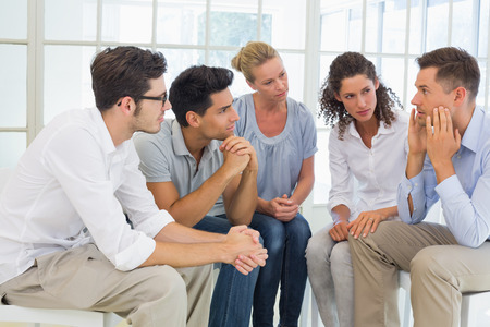 Group therapy in session sitting in a circle in a bright room photo