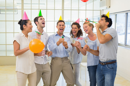 party poppers: Casual business team celebrating with champagne and party poppers in the office