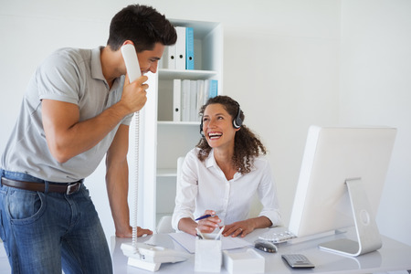 Casual business team laughing together at desk in the office photo
