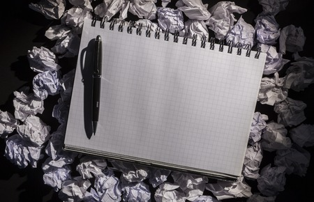 Graph paper notebook with pen on dark background photo