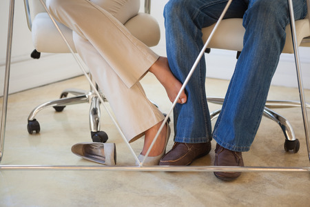 Casual businesswoman playing footsie with colleague under desk in the office