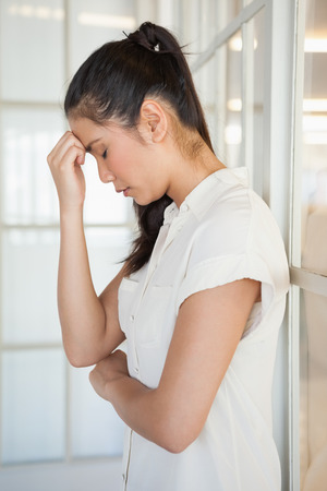 bowed head: Casual upset businesswoman with head bowed in the office
