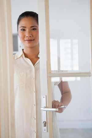 Casual businesswoman opening glass door in the office photo
