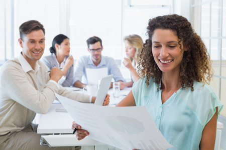 Casual businesswoman reading document during meeting in the office photo