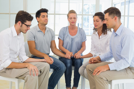Group therapy in session sitting in a circle holding hands in a bright room photo