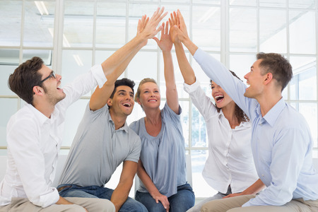 psychotherapy: Group therapy in session sitting in a circle high fiving in a bright room
