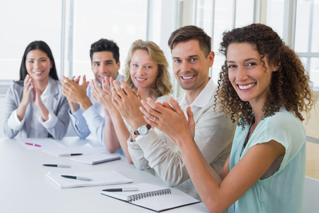 Casual business team smiling and applauding at camera in the office