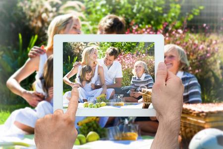 familia picnic: Pc holding tablet Mano mostrando familia feliz con un picnic Foto de archivo