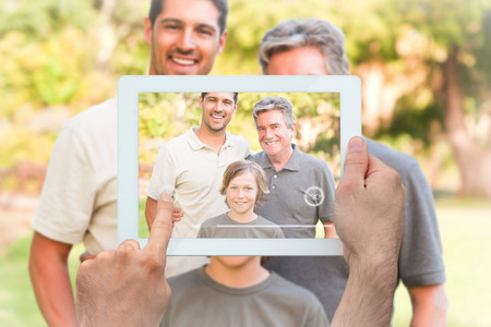 Hand holding tablet pc showing family looking at the camera in the park photo
