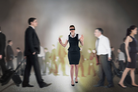 Composite image of redhead businesswoman in a blindfold walking through crowd photo