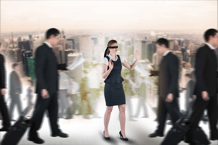 Composite image of redhead businesswoman in a blindfold walking through crowd