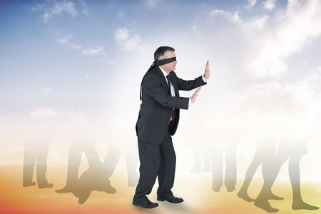 Mature businessman in a blindfold against beautiful orange and blue sky photo