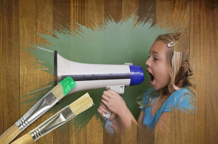 Composite image of little girl with bullhorn against wooden surface with paintbrush photo