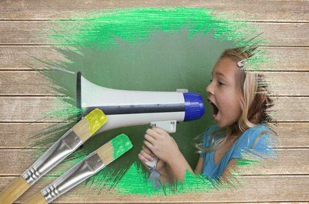 Composite image of little girl with bullhorn against wooden surface with paintbrushes photo