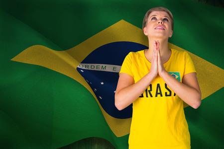 Nervous football fan in brasil tshirt against digitally generated brazil national flag photo