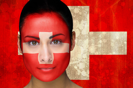 Composite image of beautiful football fan in face paint against switzerland flag in grunge effect photo