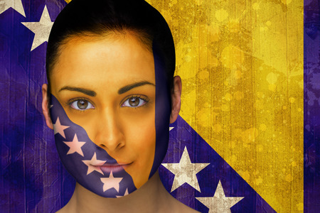 Composite image of beautiful football fan in face paint against bosnia flag in grunge effect photo