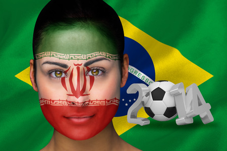Composite image of iran football fan in face paint against world cup 2014 with brasil flag photo