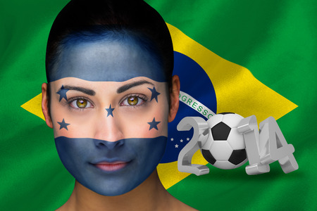 Composite image of honduras football fan in face paint against world cup 2014 with brasil flag photo