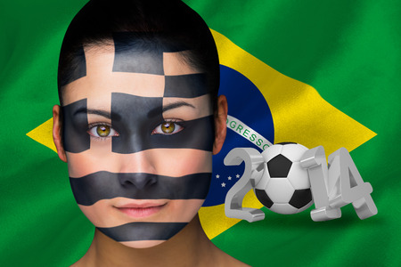 Composite image of greek football fan in face paint against world cup 2014 with brasil flag photo