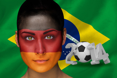 Composite image of german football fan in face paint against world cup 2014 with brasil flag photo