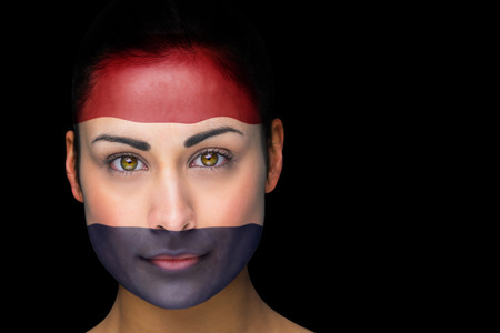 Composite image of netherlands football fan in face paint against black photo